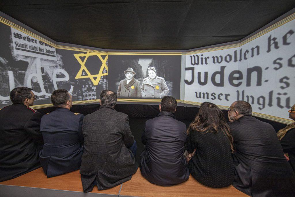 """Spettatori assistono alla videoproiezione introduttiva della mostra """"1938: l'umanità negata"""""""