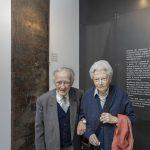 """1. Cesare Finzi con la moglie Vera alla mostra del MEIS """"Ferrara ebraica"""" vicino all'insegna della Profumeria Finzi donata al Museo."""